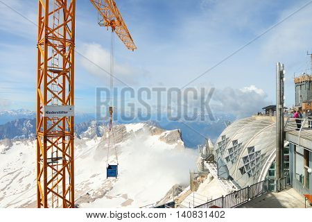 ZUGSPITZE GERMANY - JULY 5, 2016: Liebherr crane 150 EC-B on Germany's highest construction site in 2962m. Building the new Zugspitze cable car for tourists and skiers.