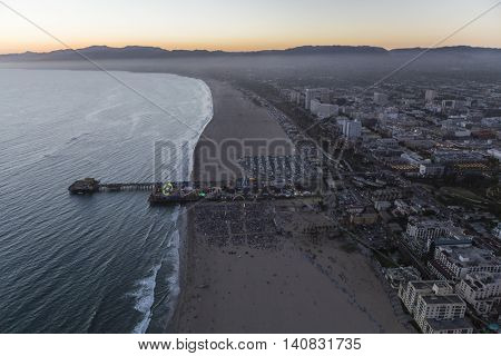 Santa Monica, California, USA - July 21, 2016:  After sunset aerial of crowds at Santa Monica beach and pier.
