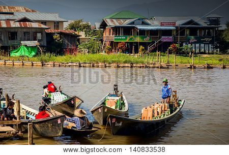 SHAN, MYANMAR - DECEMBER 2015 -  Tourists take a boat trip to Inle lake to visit villages, temples, and floating farm.  Taking a boat is a common way to enter Inle lake area.
