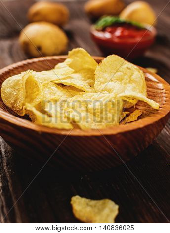 Salty potato chips snack with tomato dip on wood table