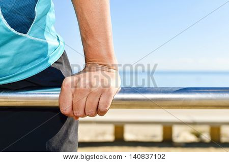 closeup of a young caucasian sportsman wearing sport clothes doing exercises in a metal bar outdoors
