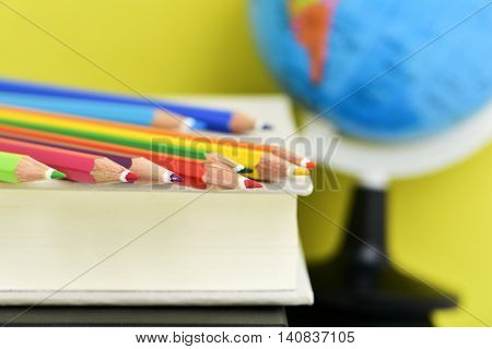 closeup of a pile of pencil crayons of different colors on a pile of books, and a terrestrial globe in the background, against a yellow background