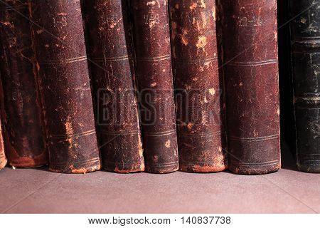Vintage library. Old book in a row on dark background