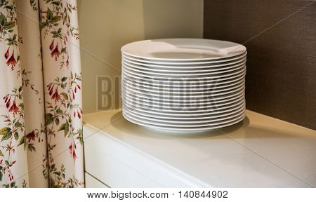 crockery and dishes concept - close up of plates on cupboard shelf