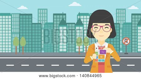 An asian woman holding modular phone. Woman with modular phone standing on a city background. Woman using modular phone. Vector flat design illustration. Horizontal layout.