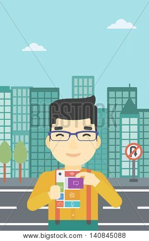 An asian man holding modular phone. Young man with modular phone on a city background. Man using modular phone. Vector flat design illustration. Vertical layout.