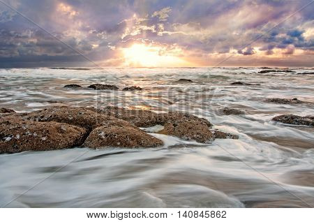 Rough ocean water moving swiftly over jagged rocks and sand.