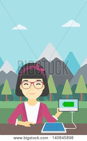 An asian woman charging tablet computer with solar panel on a background of mountains. Charging digital tablet from portable solar panel. Vector flat design illustration. Vertical layout.
