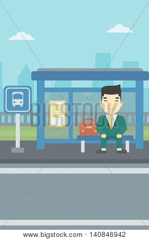 An asian young man waiting for a bus at a bus stop on a city background. Young man sitting at the bus stop. Vector flat design illustration. Vertical layout.