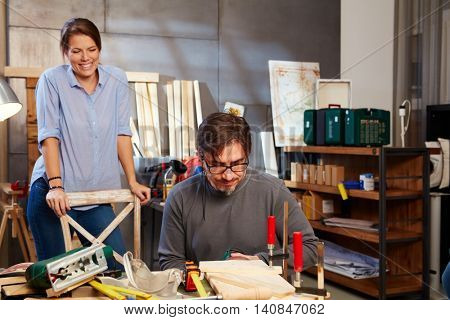 Tinkering couple working in workshop.