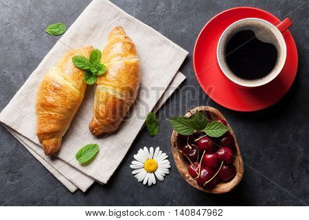 Fresh croissants, cherry berries and coffee cup on stone table. Top view. Breakfast concept