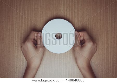 Vintage tone of hand holding a blank cd