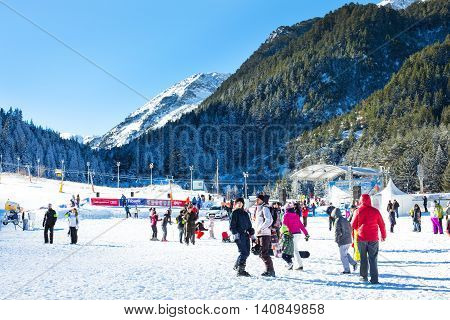 Bansko, Bulgaria - December, 12, 2015: Vibrant image of ski resort Bansko, Bulgaria, pistes and mountain with pine trees, ski slope, people walking and skiing