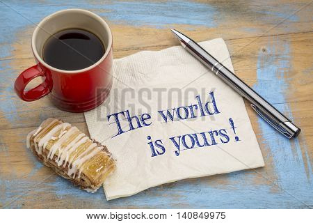 The world is yours - a positive affirmation. Handwriting on a napkin with a pen, cup of espresso coffee and cookie against grunge painted wood