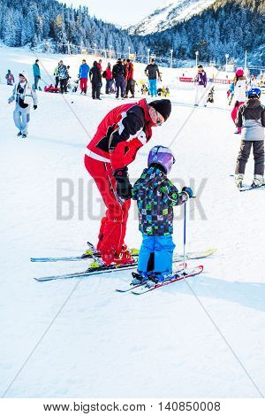 Bansko, Bulgaria - December, 12, 2015: The small child learning to ski and man on the slope in Bansko, Bulgaria