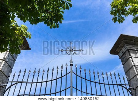Wrought iron gate with cross against blue sky