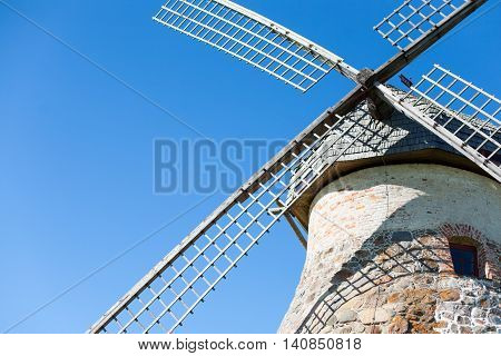 Old windmill made out of stone and wood for grinding grains