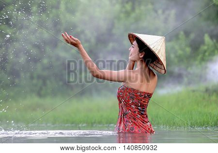Vietnamese girl was showered in the lake. Is the way of living of people in Asia.