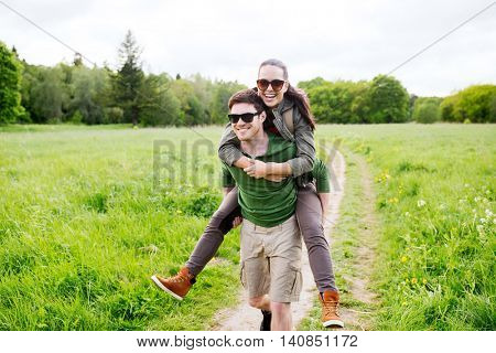 travel, hiking, backpacking, tourism and people concept - happy couple with backpacks having fun and walking along country road outdoors