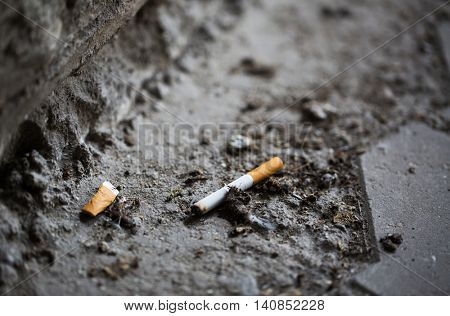 smoking, substance abuse, addiction, people and bad habits concept - close up of smoked cigarette butt on ground
