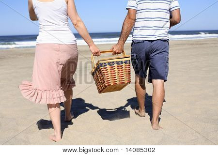 Couple holding picnic basket at beach