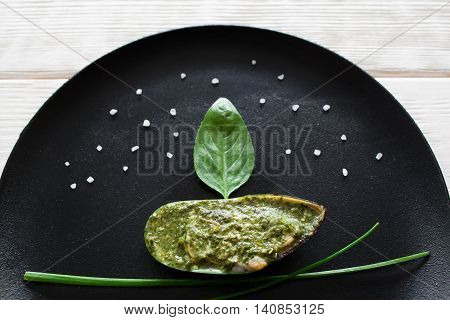 Beautifully decorated catering plate with mussel. Seafood in form of ship on black plate background