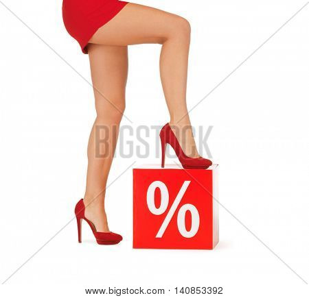 people, sale, discount and shopping concept - close up of woman legs in red shoes with percent sign