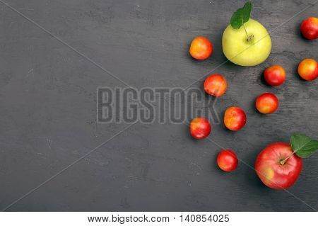 Cherry plum and apples in dark rough background with copy space top view