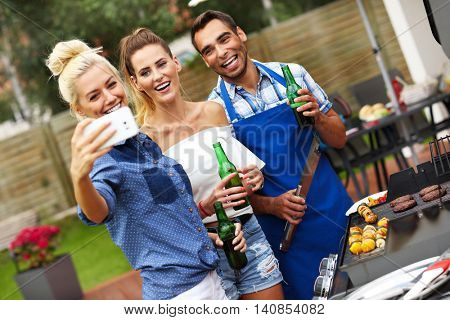 Picture presenting group of friends having barbecue party and taking selfie