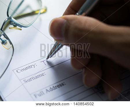 Hand with pen and glasses over application form, Completing An Employment Application Form