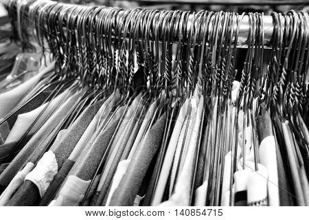 Many several metal wire hangers on pole for hanging clothing in closet storage