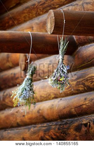 Floral Boquet of flowers hanging drying on beam of log cabin