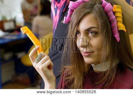 Hair curling making. Beautiful girl. Hair curlers. Professional barbers