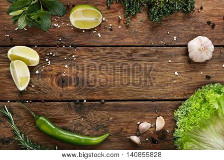 Green fresh food background on rustic wood top view with copy space. Wood planks and vegetables, cooking ingredients flat lay. Cooking concept, lime, lettuce, garlic, chili pepper, rosemary and mint.
