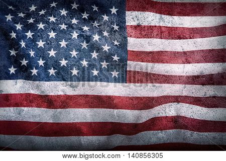 USA flag. American flagon concrete background. American flag blowing wind. Close-up. Studio shot.