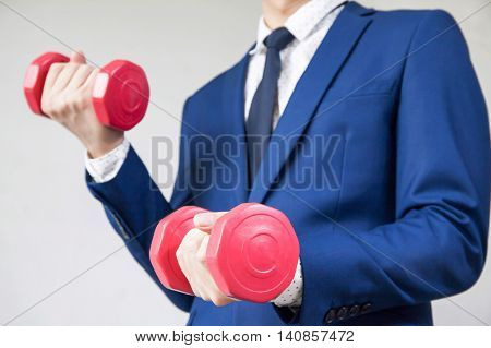 Young Businessman On Trainng And Lifting Dumbells