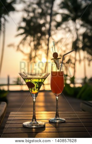 colourful cocktails on wooden table and sunbeds at pool access front beach seaview on sunset.