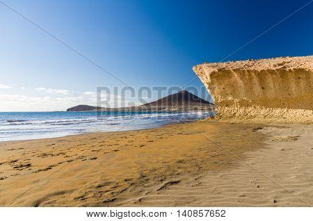 Sand and cliffed coast of Playa el Medano beach Montana Roja mountain on background Tenerife Canary islands Spain
