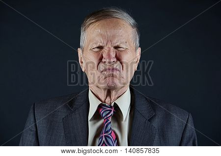 Business man smells, bad smell, senior man closeup portrait isolated on black background. Emotions, facial expression and people concept