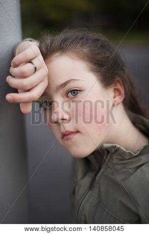 girl in pensive mood leaned against a pillar
