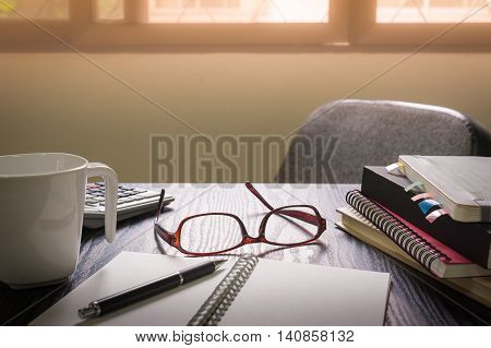 Glasses put down on table beside notebooks and pen in morning time on work day. Business working at home concept