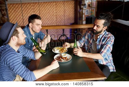 people, leisure, friendship and bachelor party concept - happy male friends drinking bottled beer and eating snacks at bar or pub