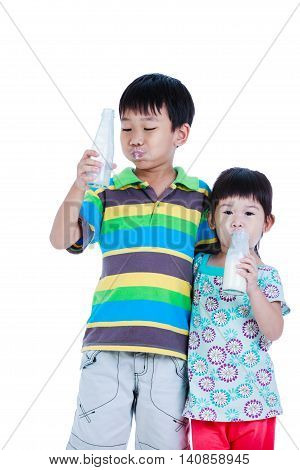 Two Asian Boy And Girl Drinking Milk, Isolated On White. Drinking Milk For Good Health.