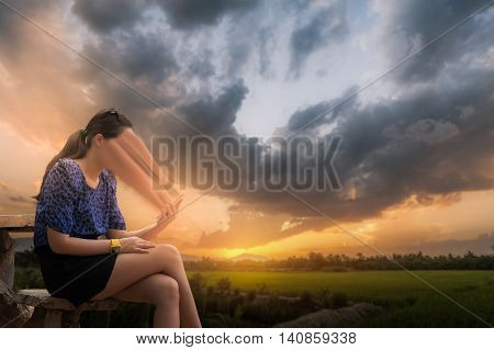Abstract scene of young woman using her smartphone seriously while sitting outdoor on wood chair in morning time on weekend with blurry nature background. Phone addiction abstract concept.