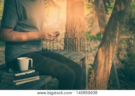 Weekend lifestyle scene of young woman using her smartphone seriously while sitting in outdoor park on wood table in morning time. Freelance business working and phone addiction concept with vintage filter effect