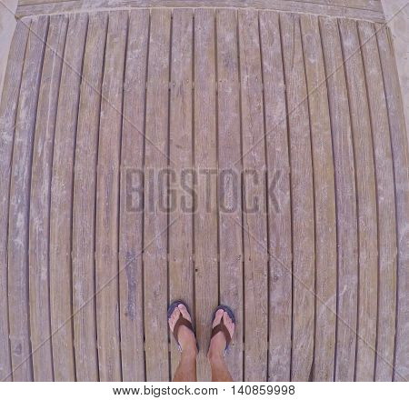 Fish eye shot of male feet in flip-flops on wooden planks.above.Copy space.