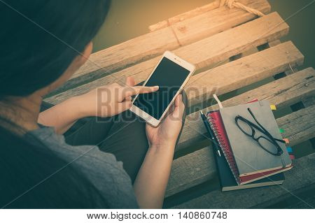 Weekend morning lifestyle. Young woman touching on mobile phone screen while sitting outdoor with notebooks pen and glasses in morning time. Freelance working and phone addiction concept with vintage filter effect