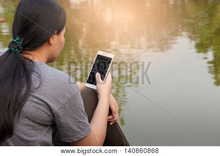 Weekend morning lifestyle. Young woman touching on mobile phone screen while sitting outdoor beside river in morning time. Freelance working and phone addiction concept