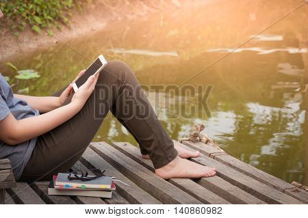 Weekend morning lifestyle. Young woman using her mobile phone seriously while sitting outdoor beside river with notebooks pen and glasses in morning time. Freelance working and phone addiction concept
