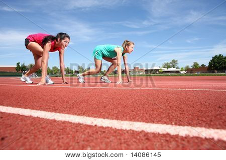 Two women on track in starting positions